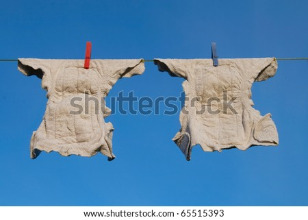 Two modern cloth diapers drying on a clothes line - stock photo