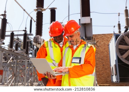 two modern electrical technicians using laptop in substation
