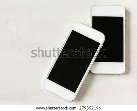 Two modern phones on wooden background - stock photo