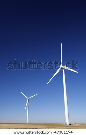 two modern windmills with clear blue sky