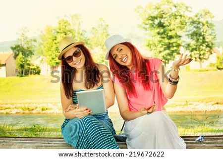 Two modern young Caucasian redhead and brunette women in park with tablet and smartphone enjoying summer. Two millennial girlfriends laughing outdoors. - stock photo