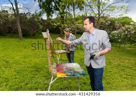 Two modest  painters standing in front of their sketchbooks painting pictures with  oils and acrylics paint during an art class in a park