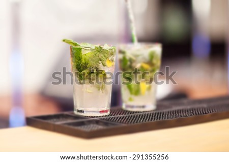 Two Mojito cocktails on a bar counter.