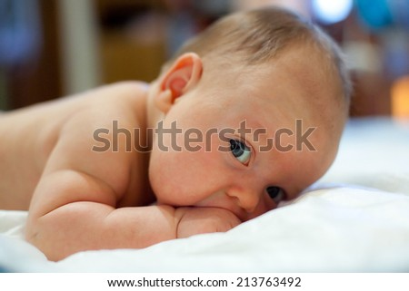 Two month old baby laying on his tummy, sucking his fist and trying to hold his head. Baby looking straight at the camera. Baby has neonatal jaundice. Selective focus on baby eye - stock photo