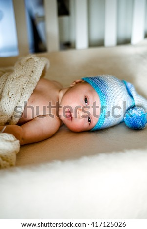Two month old baby sound asleep in his crib, with a handy toy - stock photo