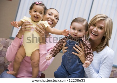 Two mothers holding baby boy and girl looking to camera - stock photo