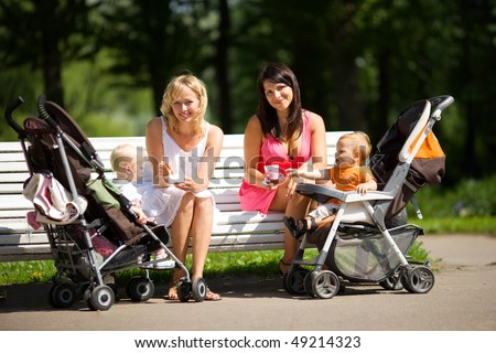 Two mothers spoon feeding their babies sitting on bench - stock photo