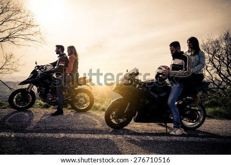 Two motorbikes driving in the nature - Friends driving racing motorcycles with their girlfriends - Group of bikers stop in a panoramic view point and look at suggestive sunset - stock photo