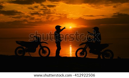 Two motorcyclists at sunset communicate. They are naberegu River, near his motocross bike. Sports equipment - stock photo