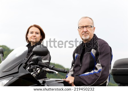 Two motorcyclists sitting on the bike - stock photo