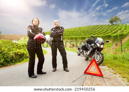 Two motorcyclists with breakdown are waiting on the street - stock photo