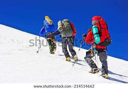Two mountain backpackers walking on snow