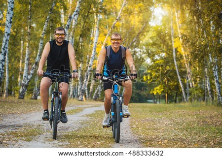 Two mountain bikers riding bike in the summer forest