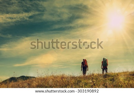 Two mountain travelers with backpacks under blue sky - stock photo