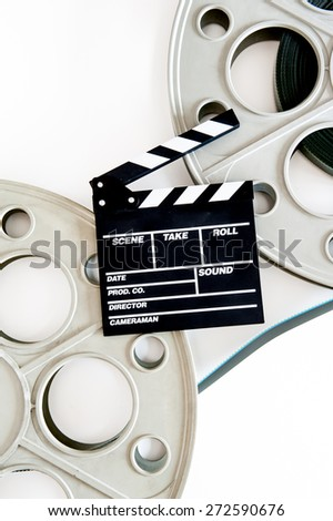 Two movie reels for 35 mm film projector with clapper board and filmstrip on neutral background, vertical frame - stock photo