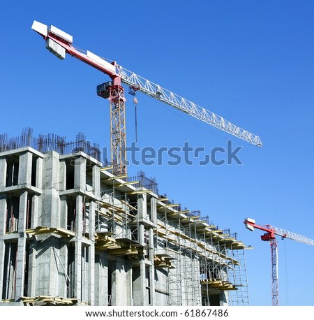 two moving yellow cranes over unfinished house - stock photo