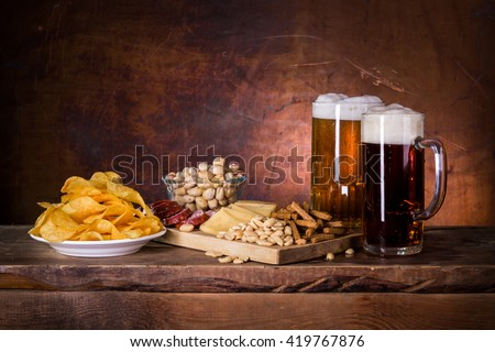 Two mugs of dark and light beer and some snacks in the European style - stock photo
