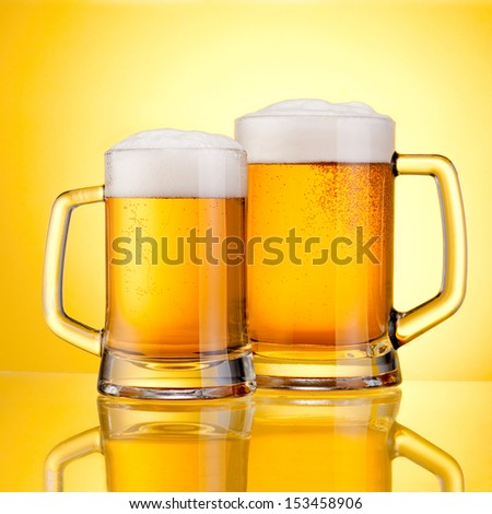 Two Mugs of fresh beer with cap of foam, isolated on yellow background - stock photo