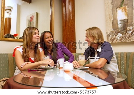 Two mulatto girls and blond man drink coffee and laugh in a restaurant. Shot in Western Cape, South Africa.