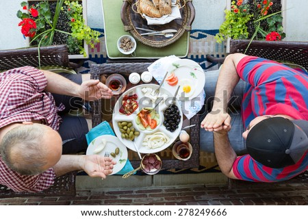 Two multi denominational men praying over food as they prepare to enjoy a healthy Mediterranean breakfast wit Turkish tea, overhead view on an outdoor patio - stock photo