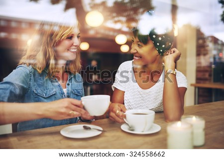 Two multi ethnic friends enjoying coffee together in a coffee shop viewed through glass with reflections as they sit at a table chatting and laughing - stock photo