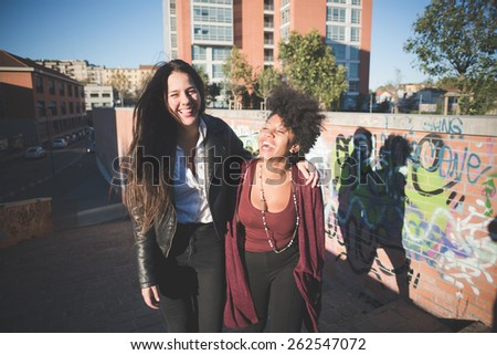 two multiethnic beautiful young woman black and caucasian having fun in town - intentional backlit - stock photo
