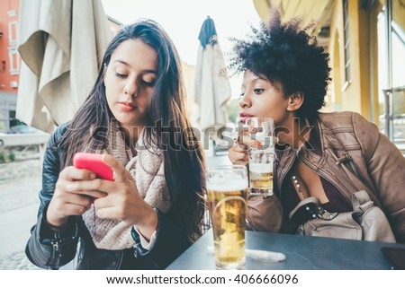 two multiethnic beautiful young woman black and caucasian using smart phone sitting in a bar, having a beer - break, technology, social network concept - stock photo