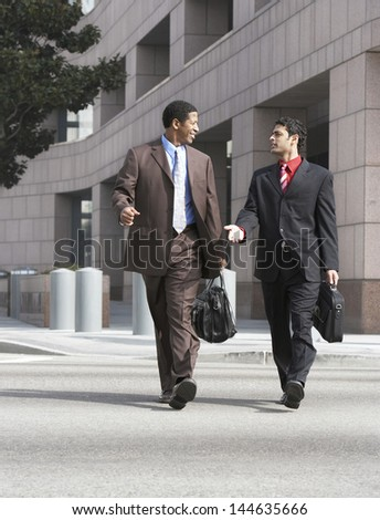 Two multiethnic business men walking on city street against buildings - stock photo