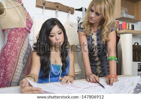 Two multiethnic female fashion designers working at desk - stock photo