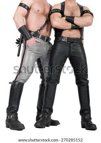 two muscular leathermen dressed in fetish gear - stock photo