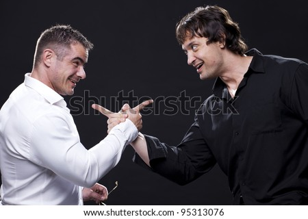 Two muscular male friends holding hands and pointing fingers at each other - stock photo
