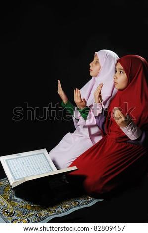 Two muslim girls with Holy Book Koran - stock photo