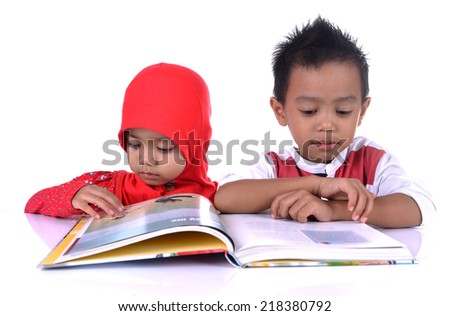 Two Muslim kids at the table reading the book, isolated on white - stock photo