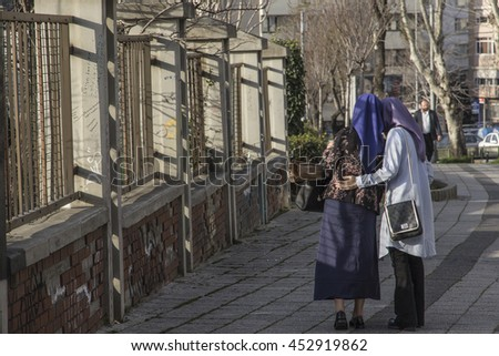 Two muslim young girls, standing and gossiping, in the shadows, next to a fence on the street. Or are they actually old catholic nuns? A concept of contradictions in religions and optical illusions.