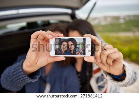 Two natural looking teenage girls who are best friends, taking a selfie outdoors with their new phone while on a road trip - stock photo
