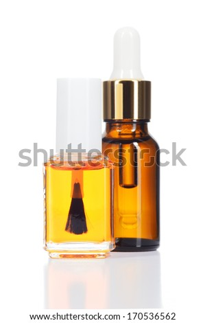 Two natural oils for beauty care isolated on white background. Nail and cuticle oil and body oil in glass bottle. - stock photo