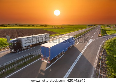 Two new trucks for different purposes driving towards the sun. Fast blurred motion drive on the freeway at beautiful sunset. Freight scene on the motorway near Belgrade, Serbia. - stock photo