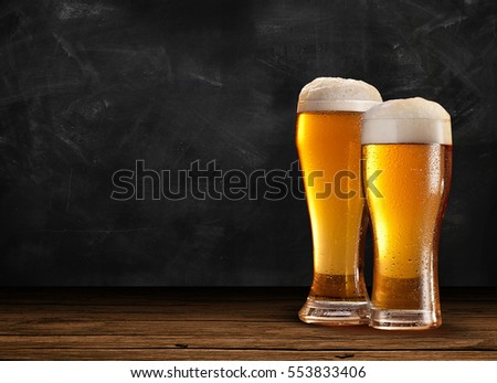 Two Nice Glasses of Beer in right on the wooden rustic table with chalk and black background on a dark pub.