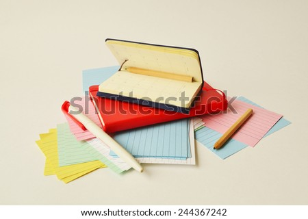 Two notebooks, colored writing paper, pen and pencils. - stock photo