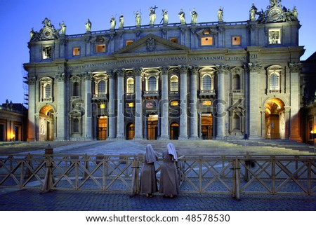 Two nuns stand looking at the The Papal Basilica of Saint Peter, Vatican City, Rome, Italy. - stock photo