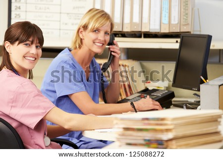 Two Nurses Working At Nurses Station - stock photo