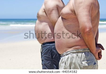 Two obesely fat men showing their bellies on the beach - stock photo