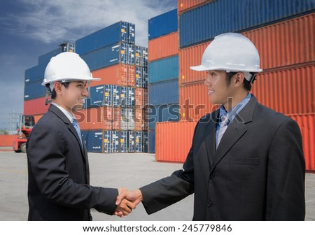 Two of Mid adult businessman shaking hands  near cargo containers for logistic concept - stock photo