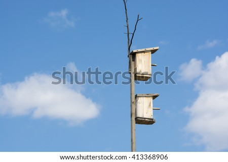 Two of the birdhouse on the background of blue sky
