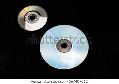 Two of the DVD or CD, one big, one small (compact) lie on a black background. On disks reflects the rainbow. - stock photo