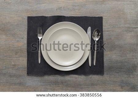 Two off-white plates with fork, knife and spoon on a black placemat on a wooden table - stock photo