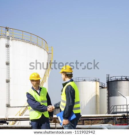Two oil industry workers shaking hands in front of the storage tanks of a petrochemical refinary - stock photo
