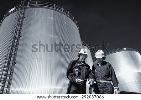 two oil workers with large fuel-tanks in background, slight blue toning concept - stock photo