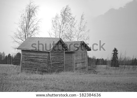 Two old barns by harvested field in rural Finland at spring, black and white, HDR effect - stock photo
