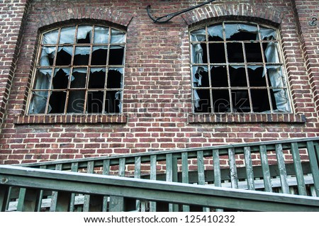Two old broken windows in old worn down building - stock photo